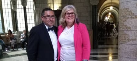 Romeo Saganash and Jennifer Preston pose in the House of Commons after Bill C-262 passes in the House.
